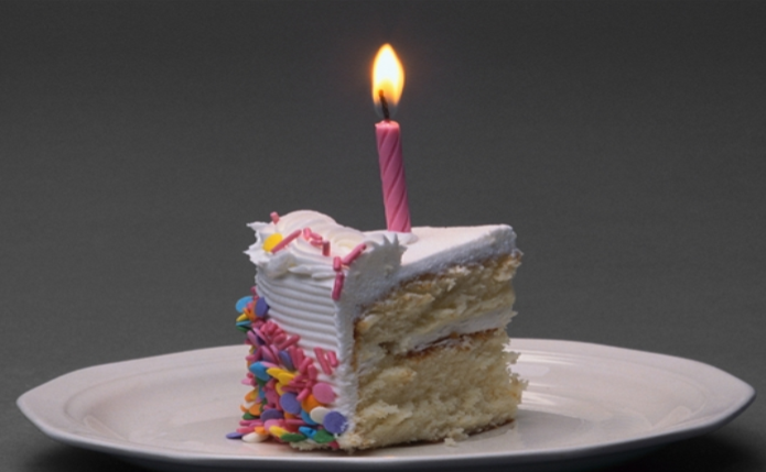 slice of birthday cake with candle on top